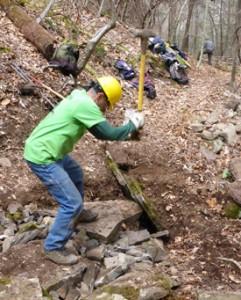 Volunteer sledgehammers rocks