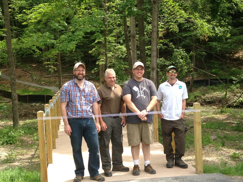 From left: Catskill Center Executive Director Jeff Senterman, DEC Senior Supervising Forester for Region 3 Jeff Rider, Trail Conference Catskills Program Coordinator Doug Senterman, and DEC Forest Preserve Forester for Region 3 Ian Dunn help open the new trail at the Catskill Interpretive Center. (Photo credit: Rosalind Dickinson)