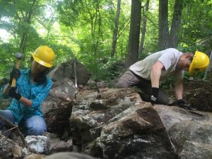 Volunteers Maitry and Robert making crush rock to finalize a stone staircase.